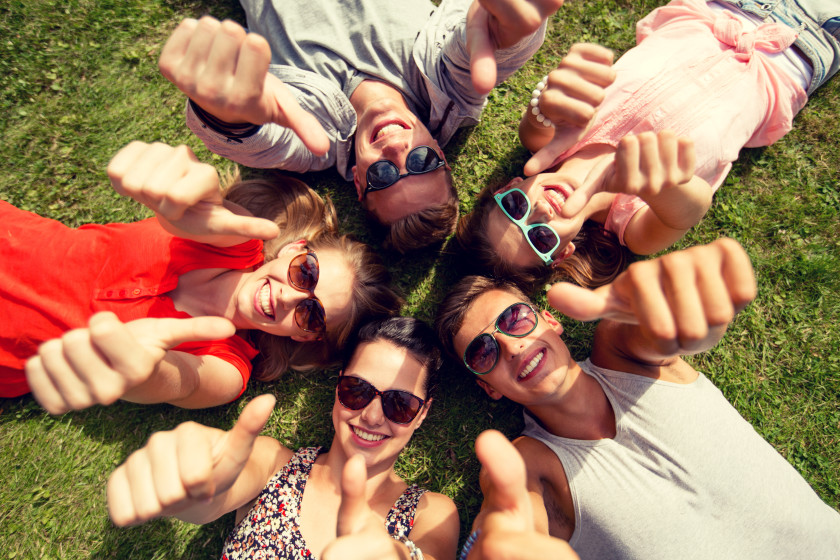 english phrases I'm easy people lying on the grass with their thumbs up